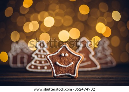 Smiling gingerbread star on wooden table, shallow dof. - stock photo