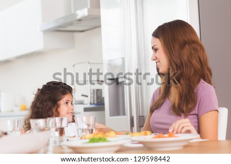 Smiling girl and her mother at the dinner table in kitchen
