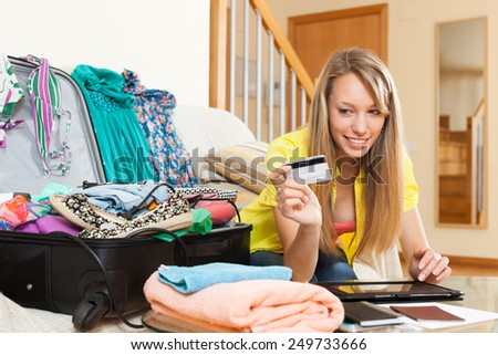 Smiling girl booking hotel for vacation online with credit card  - stock photo