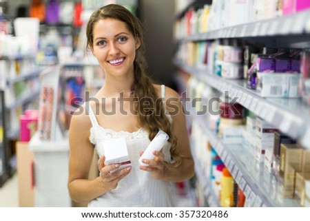 Smiling girl choosing cream for herself in the shop
