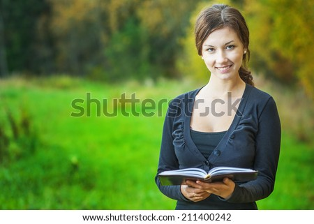 Smiling girl costs on green glade and holds in hands book. - stock photo