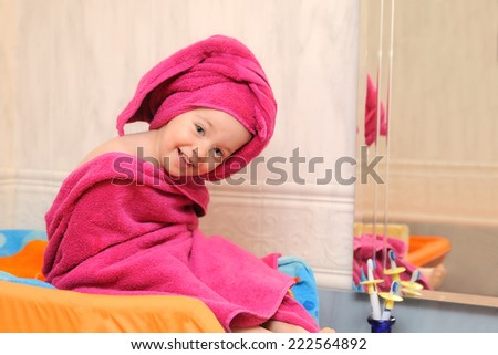smiling girl covered in a raspberry towel after a swim