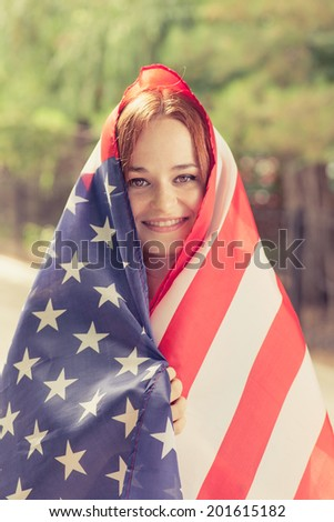 Smiling girl covered with US flag outdoors vertical shot