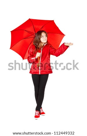smiling girl dressed in raincoat holding umbrella over white background - stock photo
