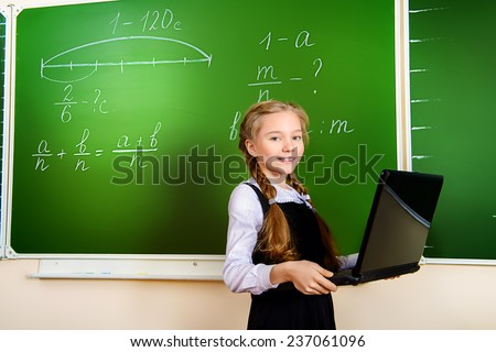 Smiling girl during a lesson with a laptop. Education.