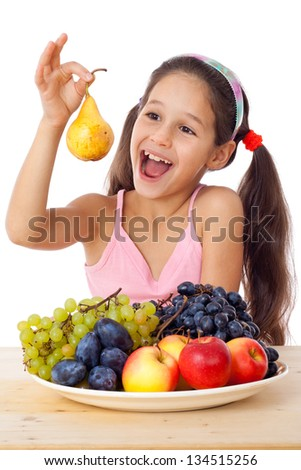 Smiling girl eating a pear on the desk with plate of fruits, isolated on white - stock photo
