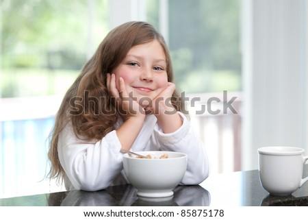 Smiling girl eating breakfast cereal - stock photo