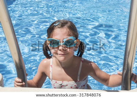 Smiling girl enjoying the pool in summer - stock photo