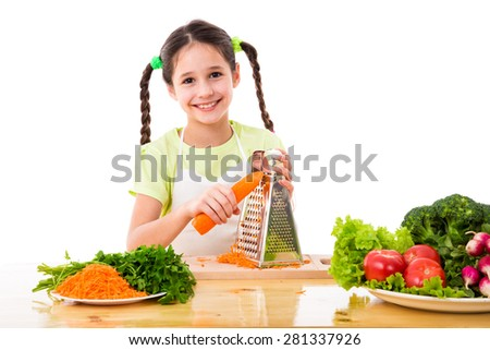 Smiling girl grate the carrots on the table with vegetables, isolated on white - stock photo