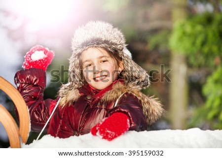 Smiling girl having fun with snowball fight - stock photo