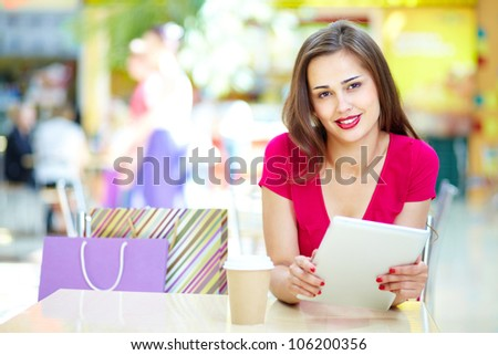 Smiling girl holding a digital pad sitting at the table in a summer cafe