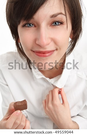 smiling girl holding a piece of chocolate in hand - stock photo