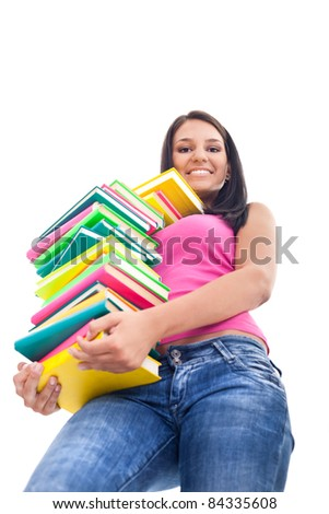smiling girl holding big stack of color books and looking down, isolated on white background