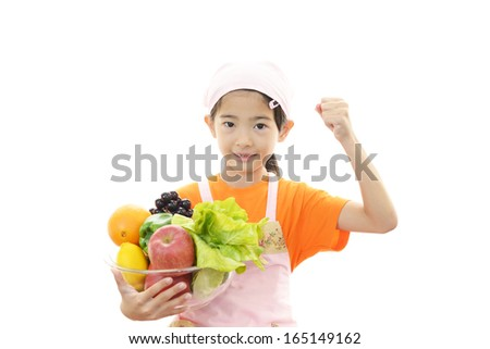 Smiling girl holding fruits and vegetables - stock photo