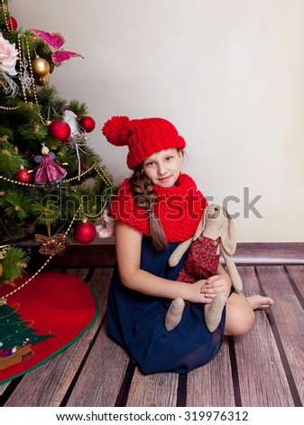 Smiling girl holding her toy while sitting by Christmas tree; preteen girl in red hat and scarf with toy - stock photo