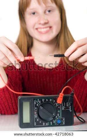 Smiling girl holding multimeter plugs - stock photo