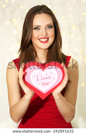 Smiling girl holding Valentines card with greetings on lights background