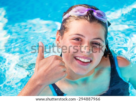 smiling girl in a pool with pink swimming goggles with the thumbs up - stock photo