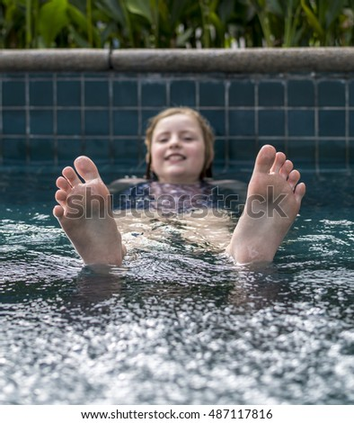 Smiling girl in a swimming pool, with her two feet nearest the camera, in focus
