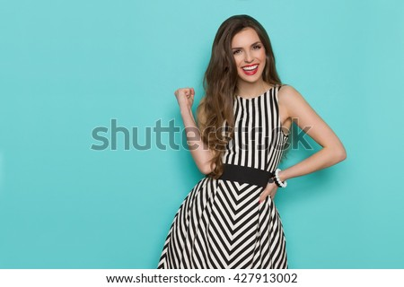 Smiling girl in black and white striped dress posing with fist raised and looking at camera, Three quarter length studio shot on turquoise background. - stock photo
