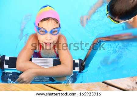 Smiling girl in blue goggles on the ladder in swimming pool - stock photo