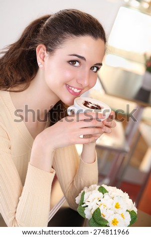 smiling  girl in coffee drinking a cup of cappuccino - stock photo