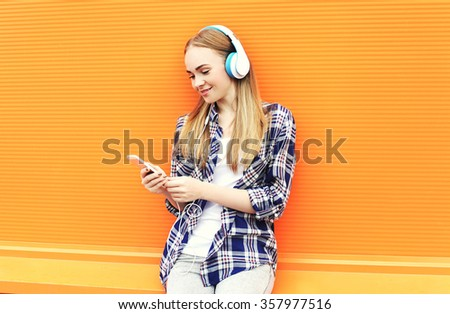 Smiling girl in headphones listens to music and using smartphone over orange background - stock photo