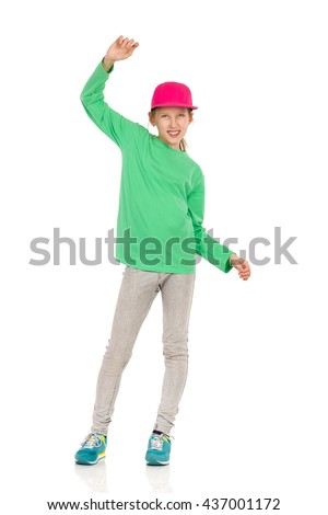 Smiling girl in pink full cap, green blouse, jeans and sneakers standing with legs apart and waving hand. Full length studio shot isolated on white. - stock photo