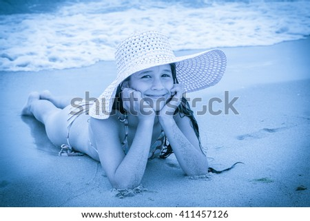 Smiling girl in pink hat on the beach lying down on the sand near water, blue toned picture - stock photo