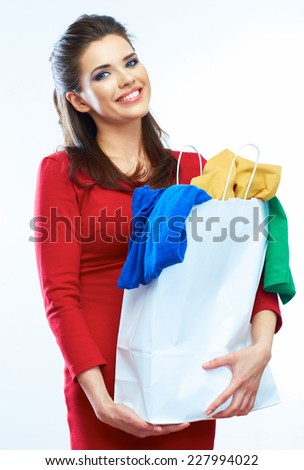 smiling girl in red dress holding shopping bag. standing against white background.