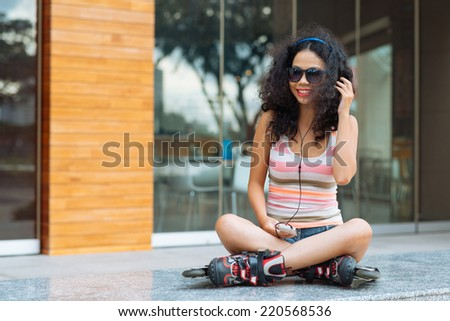 Smiling girl in roller skates sitting outdoors and listening to the music in her phone - stock photo