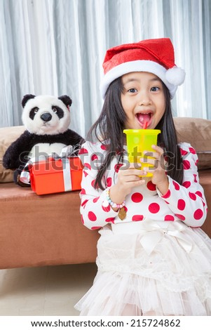 smiling girl in santa helper hat and holding glass drinking water with teddy bear sitting on isolated white background.