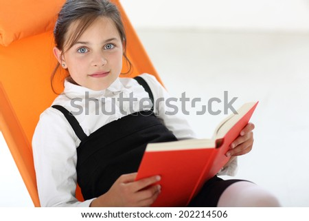 Smiling girl .Joyful girl reading a book sitting on the orange chair  - stock photo