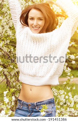 Smiling girl jumping against blossom trees background - stock photo