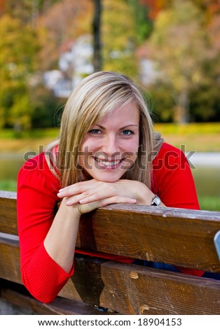 smiling girl leaning on a parkbench in autumn