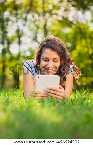 Smiling girl lying in grass with tablet