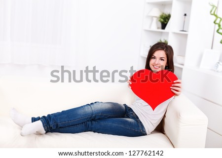 Smiling girl lying on sofa showing big paper heart to us