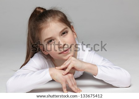 Smiling girl lying on the studio floor - stock photo
