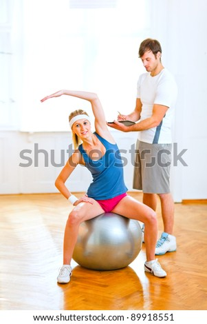 Smiling girl making exercises on fitness ball under the supervision of personal trainer - stock photo