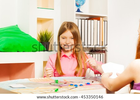 Smiling girl making her move at the gaming table - stock photo