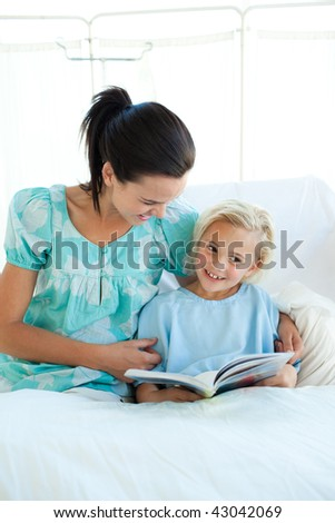 Smiling girl on a hospital bed reading with her mother - stock photo