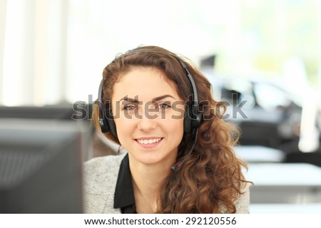 Smiling girl - operator in headphones, sitting at the computer. Customer service agent  - stock photo