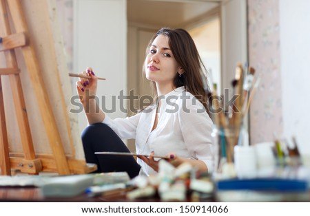 Smiling girl paints on canvas with oil colors in workshop - stock photo