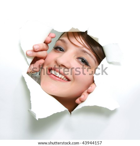 smiling girl peeping through hole in paper - stock photo