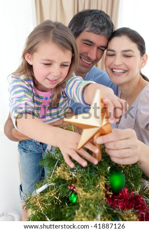Smiling girl placing a Christmas star on the top of a tree - stock photo