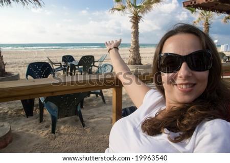 smiling girl point to the sea beach - stock photo