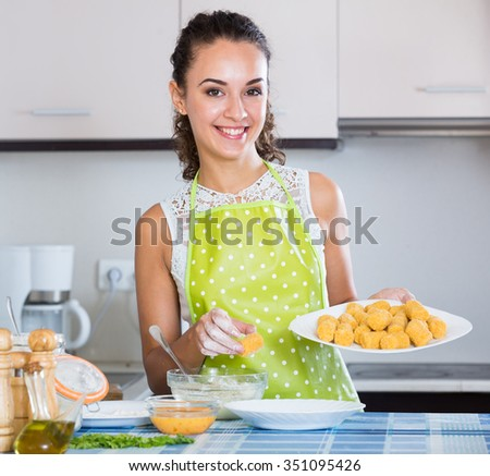 Smiling girl preparing croquettes for tasty dinner at home
