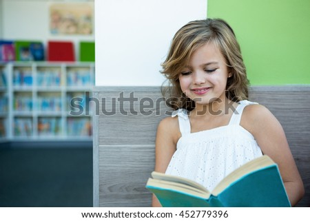 Smiling girl reading book while sitting on bench in school library - stock photo