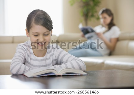Smiling girl reading book with mother in background at home - stock photo