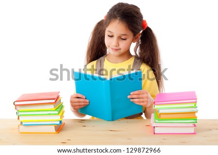 Smiling girl reading the book on the desk with stack of books, isolated on white